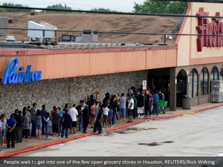 People wait to get into one of the few open grocery stores in Houston. REUTERS/Rick Wilking