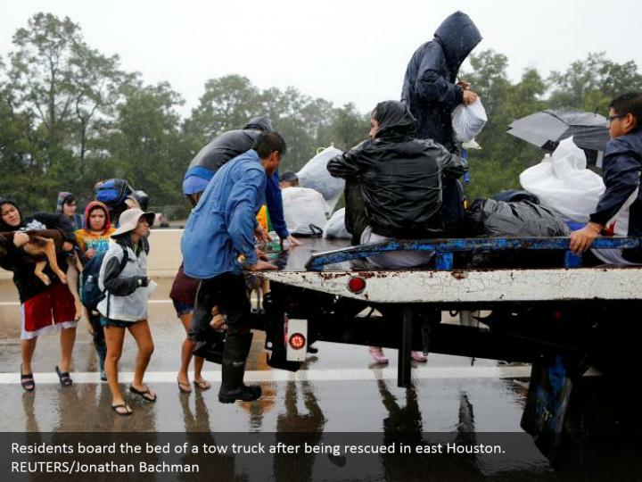 Residents board the bed of a tow truck after being rescued in east Houston. REUTERS/Jonathan Bachman