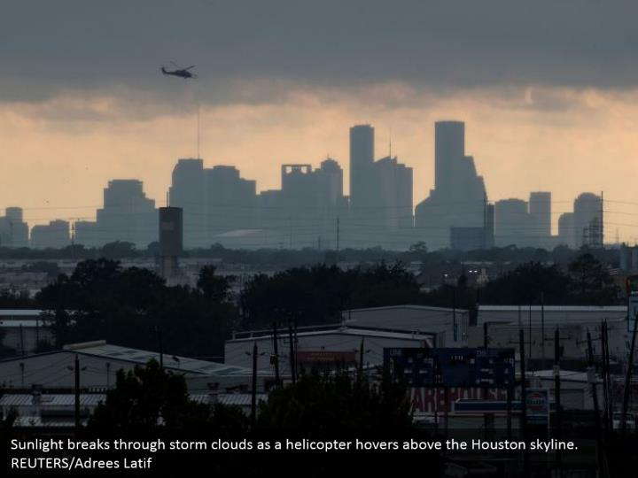 Sunlight breaks through storm clouds as a helicopter hovers above the Houston skyline. REUTERS/Adrees Latif