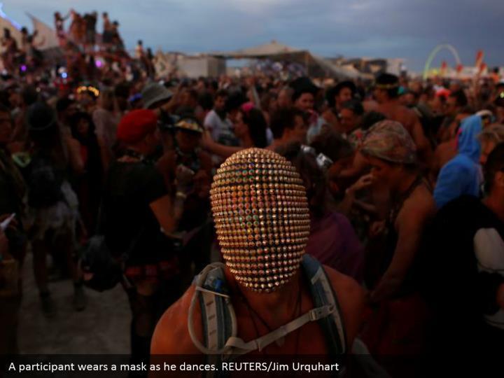 A participant wears a mask as he dances. REUTERS/Jim Urquhart