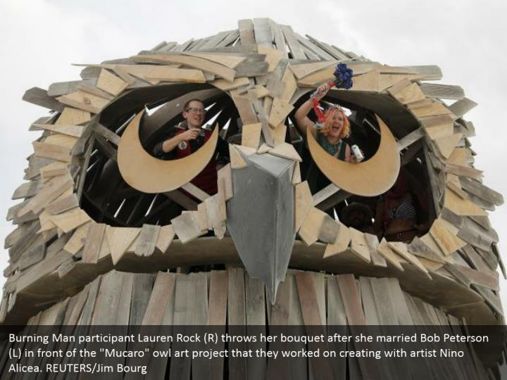 """Burning Man participant Lauren Rock (R) throws her bouquet after she married Bob Peterson (L) in front of the """"Mucaro"""" owl art project that they worked on creating with artist Nino Alicea. REUTERS/Jim Bourg"""