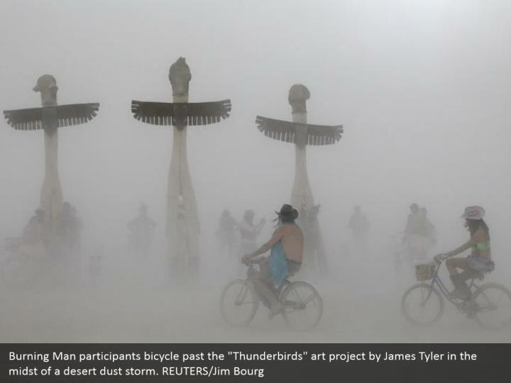 """Burning Man participants bicycle past the """"Thunderbirds"""" art project by James Tyler in the midst of a desert dust storm. REUTERS/Jim Bourg"""