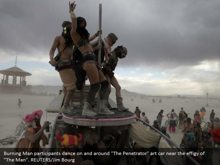 """Burning Man participants dance on and around """"The Penetrator"""" art car near the effigy of """"The Man"""". REUTERS/Jim Bourg"""