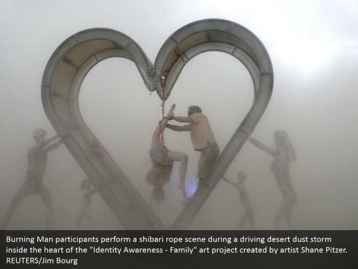 """Burning Man participants perform a shibari rope scene during a driving desert dust storm inside the heart of the """"Identity Awareness - Family"""" art project created by artist Shane Pitzer. REUTERS/Jim Bourg"""