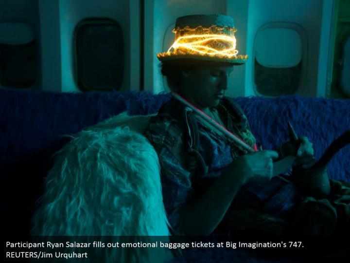 Participant Ryan Salazar fills out emotional baggage tickets at Big Imagination's 747. REUTERS/Jim Urquhart