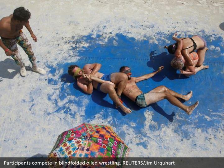 Participants compete in blindfolded oiled wrestling. REUTERS/Jim Urquhart