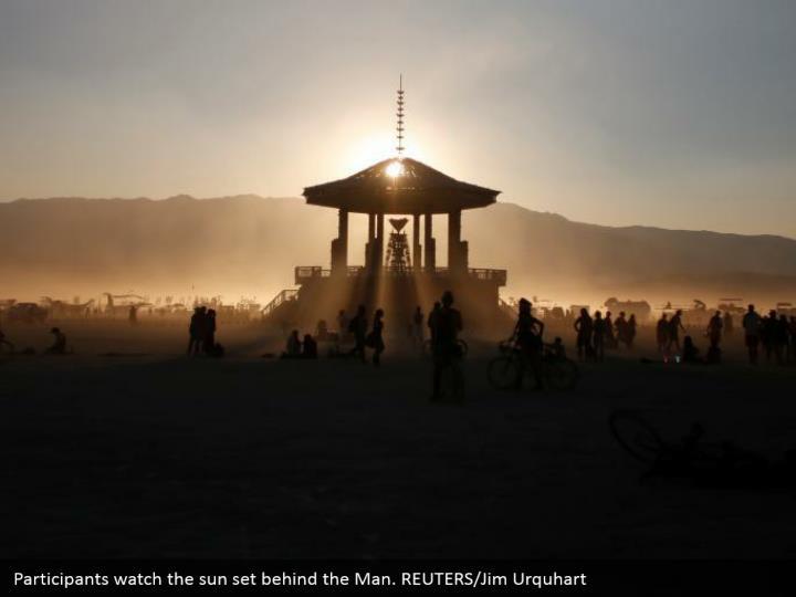 Participants watch the sun set behind the Man. REUTERS/Jim Urquhart