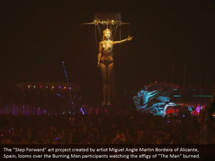 """The """"Step Forward"""" art project created by artist Miguel Angle Martin Bordera of Alicante, Spain, looms over the Burning Man participants watching the effigy of """"The Man"""" burned."""