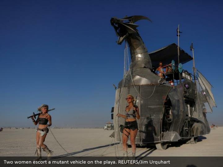 Two women escort a mutant vehicle on the playa. REUTERS/Jim Urquhart