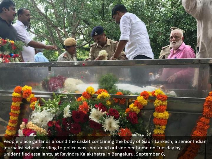 People place garlands around the casket containing the body of Gauri Lankesh, a senior Indian journalist who according to police was shot dead outside her home on Tuesday by unidentified assailants, at Ravindra Kalakshetra in Bengaluru, September 6,