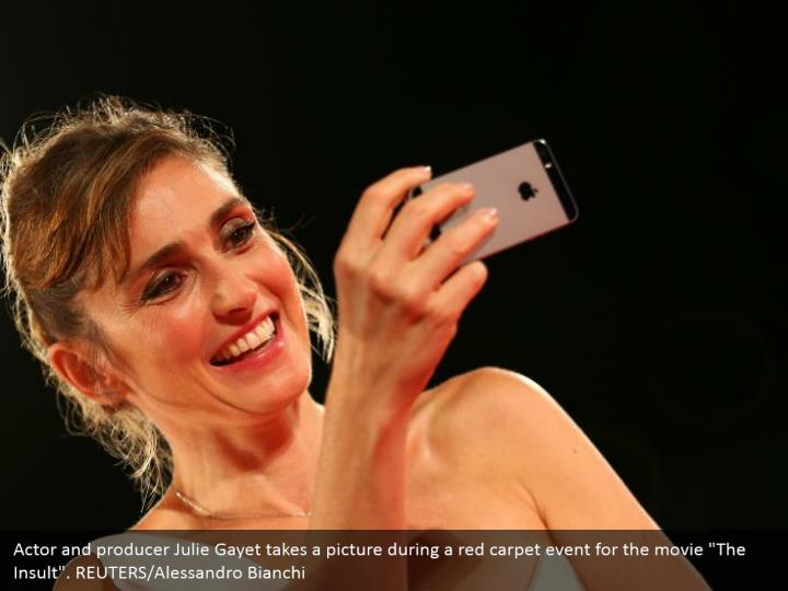 "Actor and producer Julie Gayet takes a picture during a red carpet event for the movie ""The Insult"". REUTERS/Alessandro Bianchi"