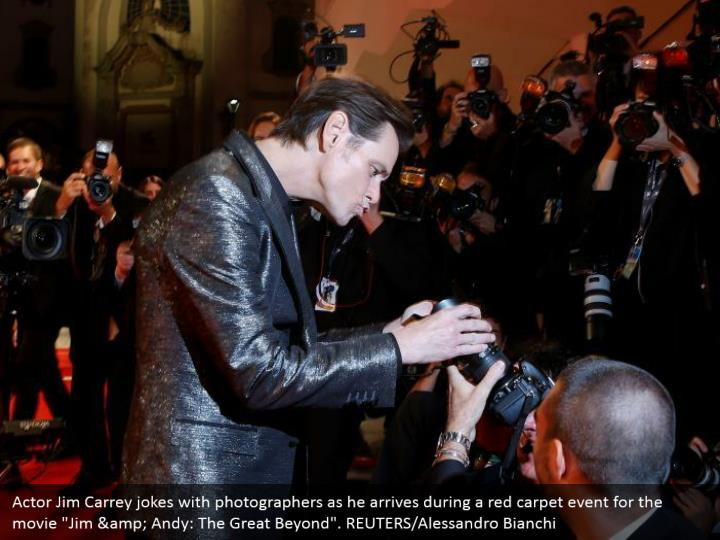 "Actor Jim Carrey jokes with photographers as he arrives during a red carpet event for the movie ""Jim & Andy: The Great Beyond"". REUTERS/Alessandro Bianchi"