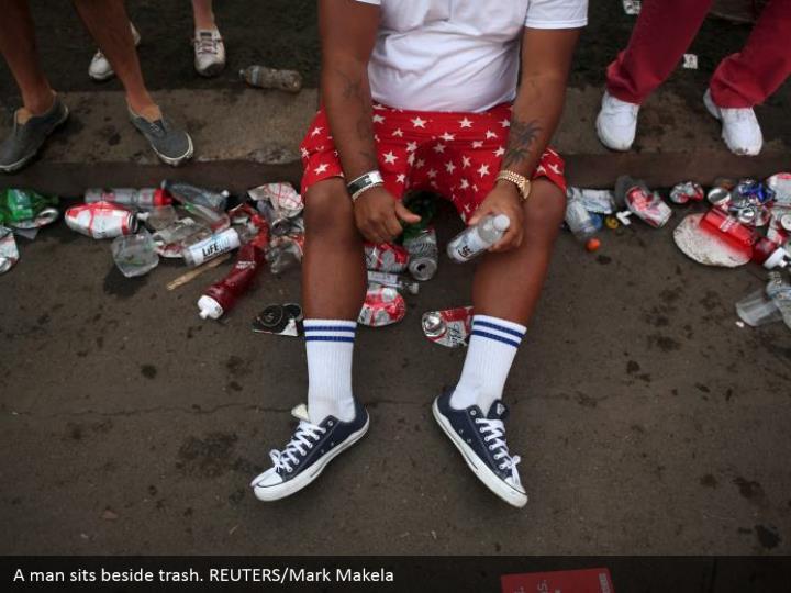 A man sits beside trash. REUTERS/Mark Makela