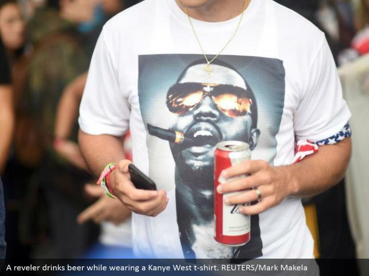 A reveler drinks beer while wearing a Kanye West t-shirt. REUTERS/Mark Makela