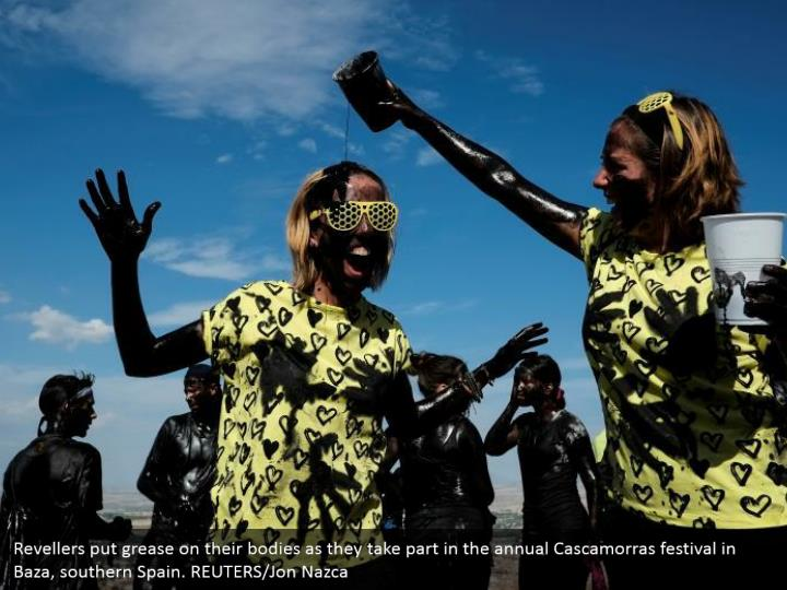 Revellers put grease on their bodies as they take part in the annual Cascamorras festival in Baza, southern Spain. REUTERS/Jon Nazca
