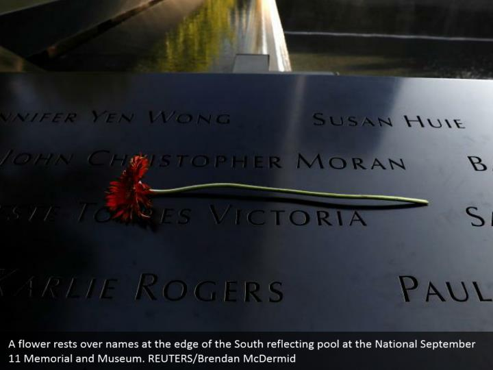 A flower rests over names at the edge of the South reflecting pool at the National September 11 Memorial and Museum. REUTERS/Brendan McDermid