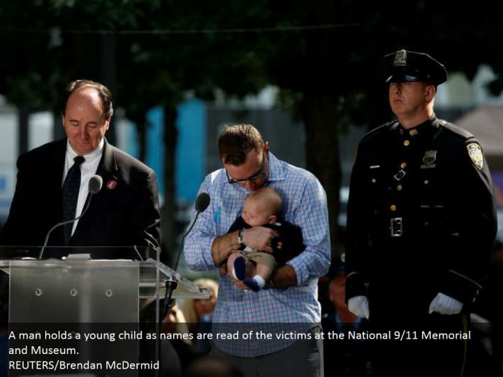 A man holds a young child as names are read of the victims at the National 9/11 Memorial and Museum.  REUTERS/Brendan McDermid