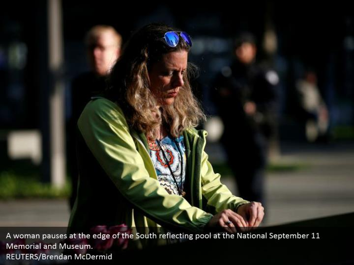 A woman pauses at the edge of the South reflecting pool at the National September 11 Memorial and Museum.  REUTERS/Brendan McDermid