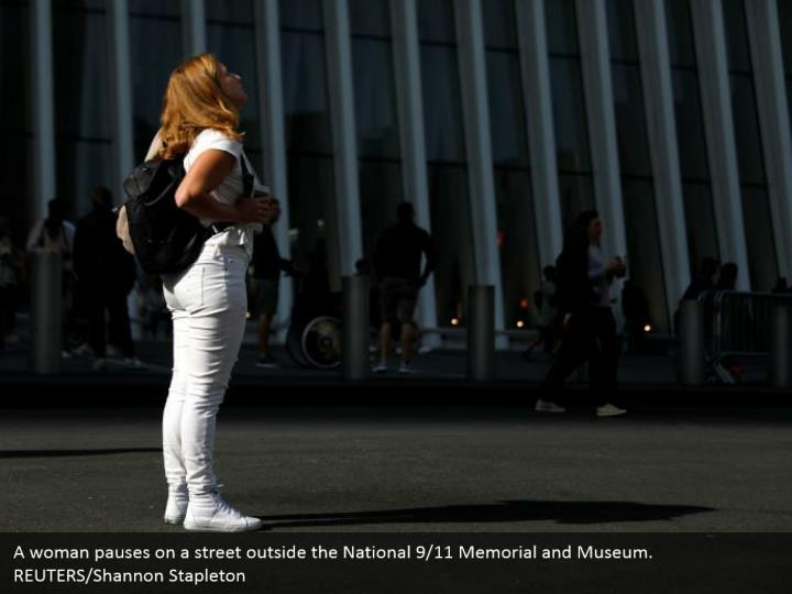 A woman pauses on a street outside the National 9/11 Memorial and Museum.  REUTERS/Shannon Stapleton