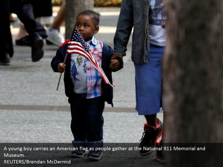 A young boy carries an American flag as people gather at the National 911 Memorial and Museum.  REUTERS/Brendan McDermid