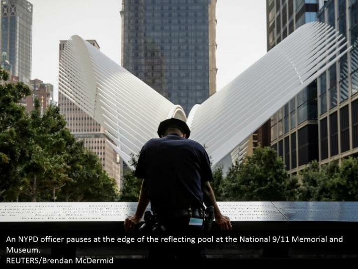 An NYPD officer pauses at the edge of the reflecting pool at the National 9/11 Memorial and Museum.  REUTERS/Brendan McDermid