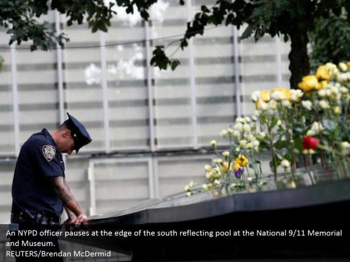 An NYPD officer pauses at the edge of the south reflecting pool at the National 9/11 Memorial and Museum.  REUTERS/Brendan McDermid