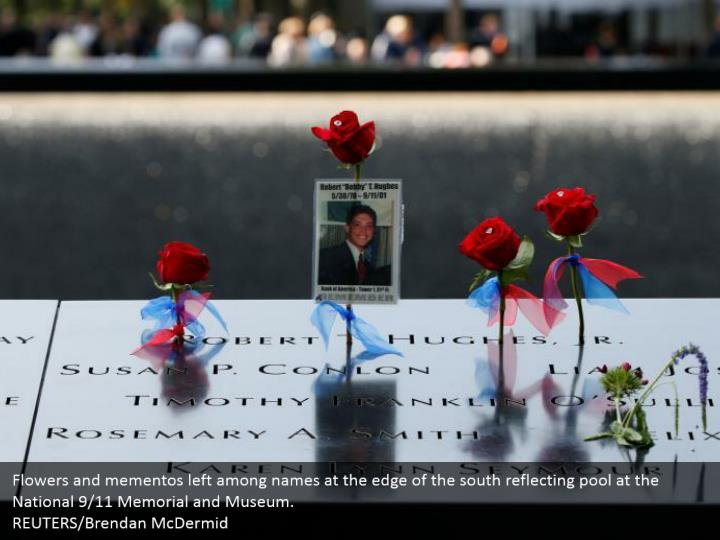 Flowers and mementos left among names at the edge of the south reflecting pool at the National 9/11 Memorial and Museum.  REUTERS/Brendan McDermid