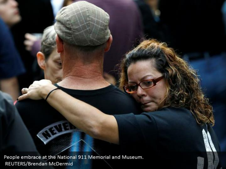 People embrace at the National 911 Memorial and Museum.  REUTERS/Brendan McDermid