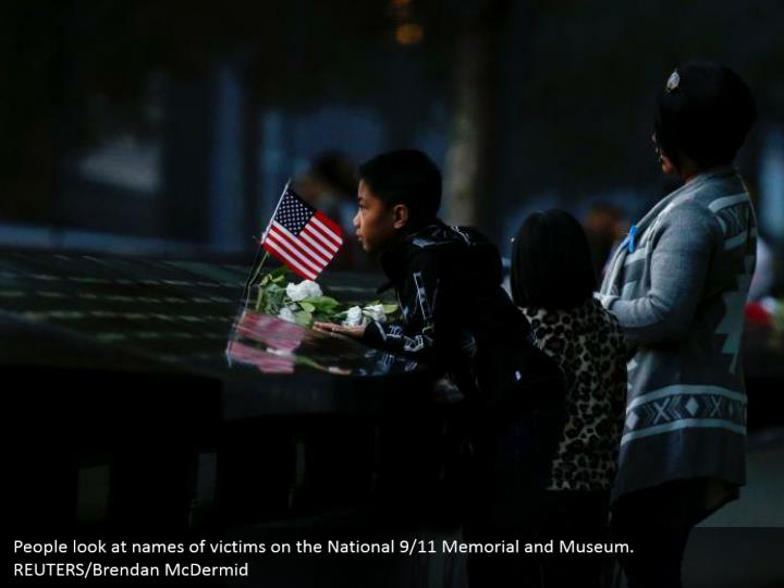 People look at names of victims on the National 9/11 Memorial and Museum. REUTERS/Brendan McDermid