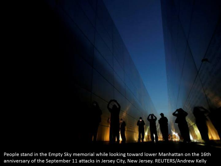 People stand in the Empty Sky memorial while looking toward lower Manhattan on the 16th anniversary of the September 11 attacks in Jersey City, New Jersey. REUTERS/Andrew Kelly