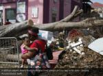 a woman passes debris from hurricane irma strewn
