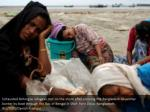 exhausted rohingya refugees rest on the shore