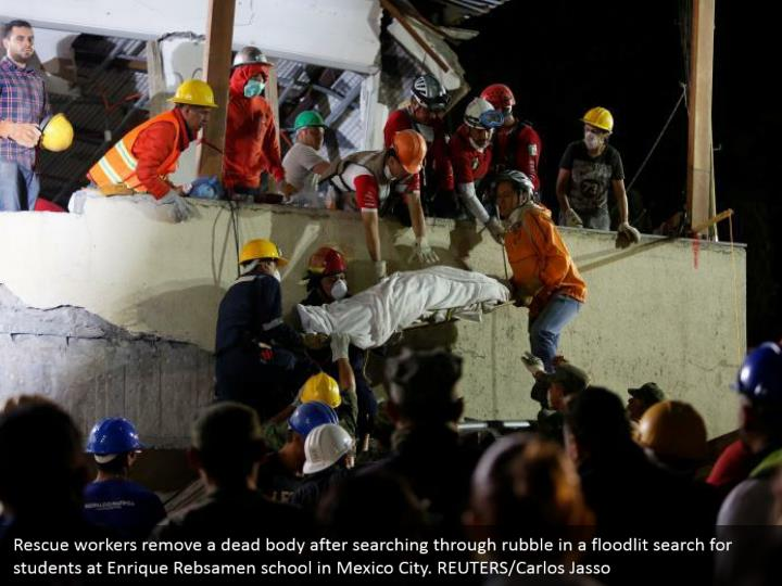 Rescue workers remove a dead body after searching