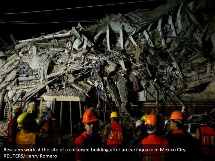 Rescuers work at the site of a collapsed building