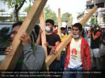 volunteers carry wooden beams to secure buildings