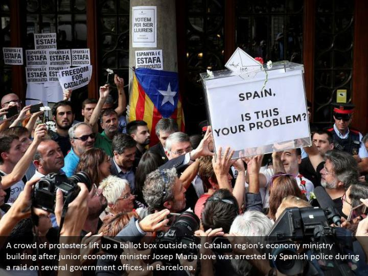 A crowd of protesters lift up a ballot box outside the Catalan region's economy ministry building after junior economy minister Josep Maria Jove was arrested by Spanish police during a raid on several government offices, in Barcelona.