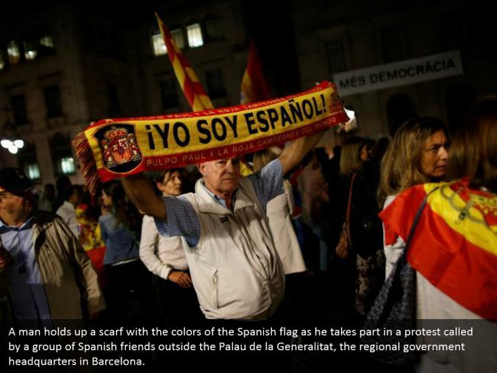 A man holds up a scarf with the colors of the Spanish flag as he takes part in a protest called by a group of Spanish friends outside the Palau de la Generalitat, the regional government headquarters in Barcelona.