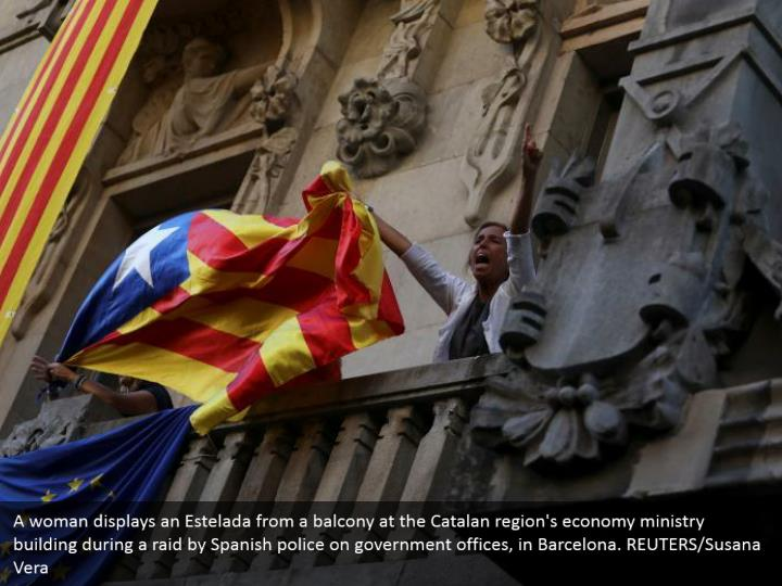 A woman displays an Estelada from a balcony at the Catalan region's economy ministry building during a raid by Spanish police on government offices, in Barcelona. REUTERS/Susana Vera