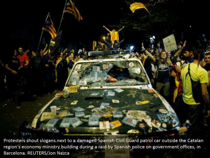 Protesters shout slogans next to a damaged Spanish Civil Guard patrol car outside the Catalan region's economy ministry building during a raid by Spanish police on government offices, in Barcelona. REUTERS/Jon Nazca