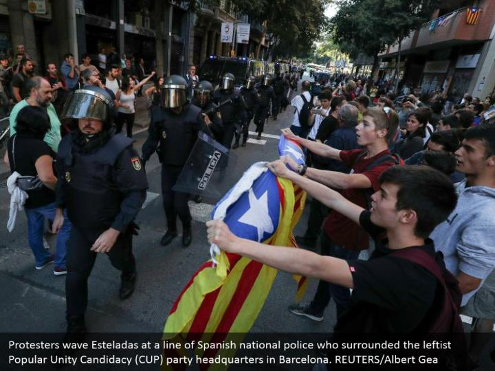 Protesters wave Esteladas at a line of Spanish national police who surrounded the leftist Popular Unity Candidacy (CUP) party headquarters in Barcelona. REUTERS/Albert Gea