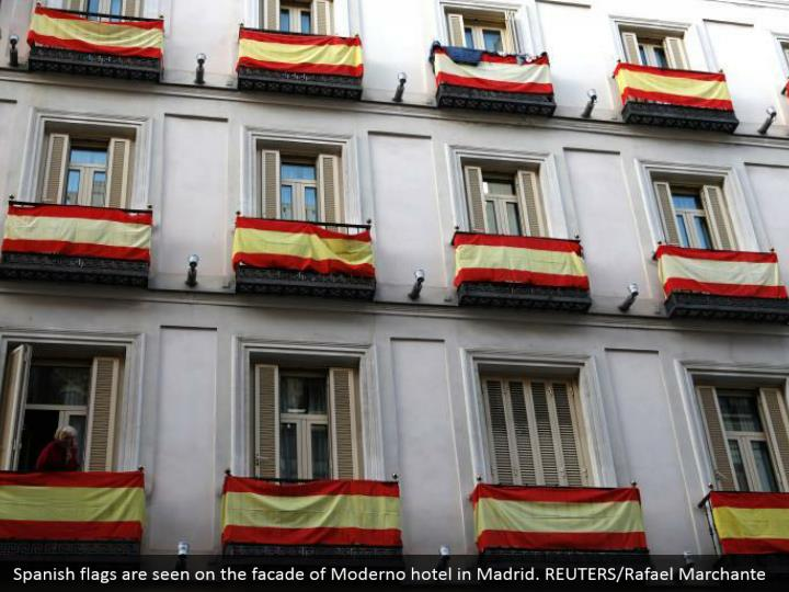 Spanish flags are seen on the facade of Moderno hotel in Madrid. REUTERS/Rafael Marchante