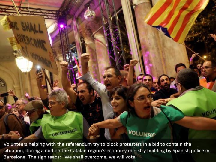 """Volunteers helping with the referendum try to block protesters in a bid to contain the situation, during a raid on the Catalan region's economy ministry building by Spanish police in Barcelona. The sign reads: """"We shall overcome, we will vote."""