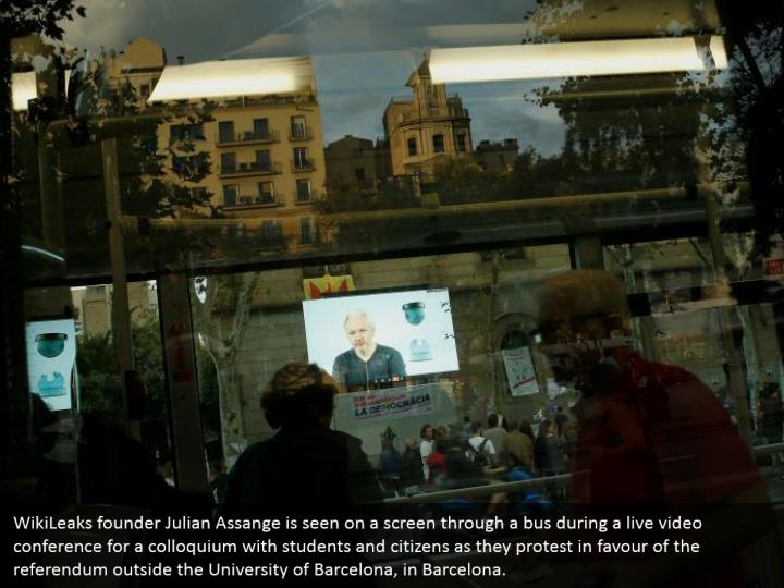 WikiLeaks founder Julian Assange is seen on a screen through a bus during a live video conference for a colloquium with students and citizens as they protest in favour of the referendum outside the University of Barcelona, in Barcelona.