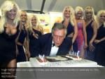 hugh hefner leans over a giant birthday cake