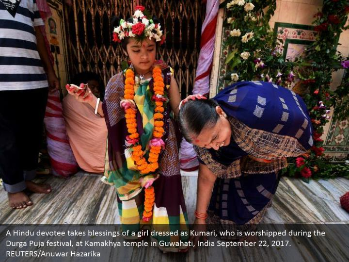 A Hindu devotee takes blessings of a girl dressed as Kumari, who is worshipped during the Durga Puja festival, at Kamakhya temple in Guwahati, India September 22, 2017. REUTERS/Anuwar Hazarika