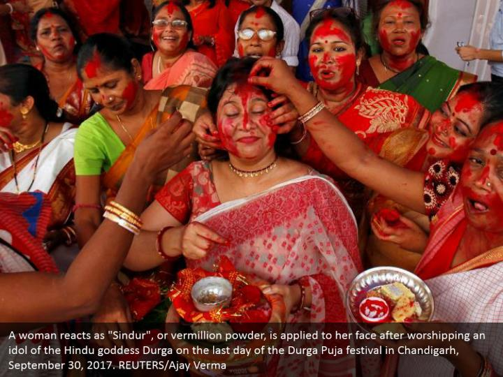 "A woman reacts as ""Sindur"", or vermillion powder, is applied to her face after worshipping an idol of the Hindu goddess Durga on the last day of the Durga Puja festival in Chandigarh, September 30, 2017. REUTERS/Ajay Verma"