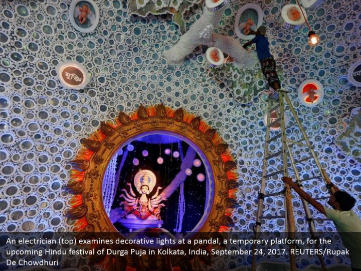 An electrician (top) examines decorative lights at a pandal, a temporary platform, for the upcoming Hindu festival of Durga Puja in Kolkata, India, September 24, 2017. REUTERS/Rupak De Chowdhuri