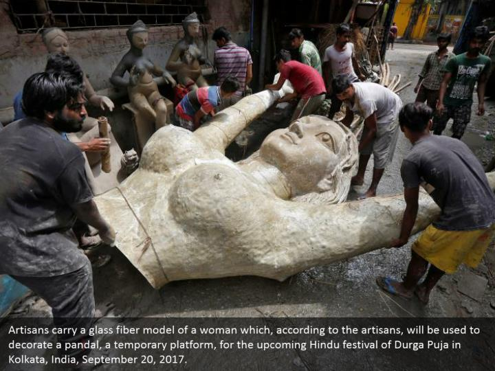 Artisans carry a glass fiber model of a woman which, according to the artisans, will be used to decorate a pandal, a temporary platform, for the upcoming Hindu festival of Durga Puja in Kolkata, India, September 20, 2017.