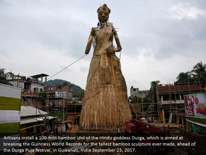 Artisans install a 100-foot bamboo idol of the Hindu goddess Durga, which is aimed at breaking the Guinness World Records for the tallest bamboo sculpture ever made, ahead of the Durga Puja festival, in Guwahati, India September 23, 2017.