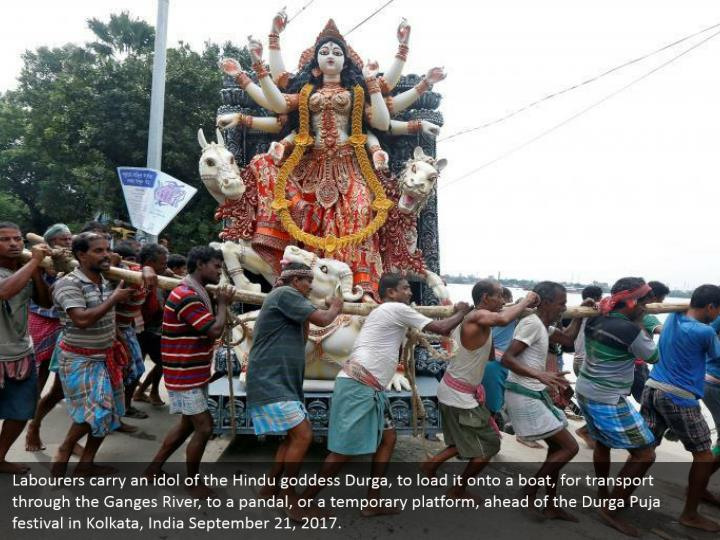 Labourers carry an idol of the Hindu goddess Durga, to load it onto a boat, for transport through the Ganges River, to a pandal, or a temporary platform, ahead of the Durga Puja festival in Kolkata, India September 21, 2017.